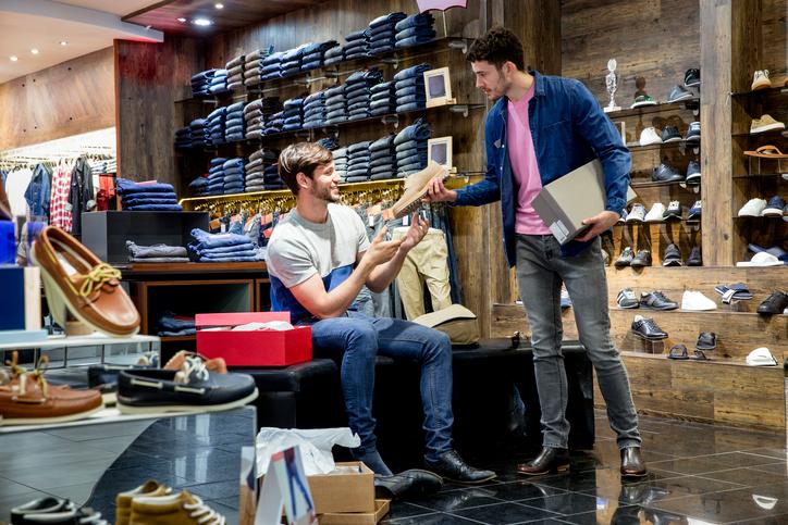 Un client dans un magasin de chaussures échange avec un vendeur